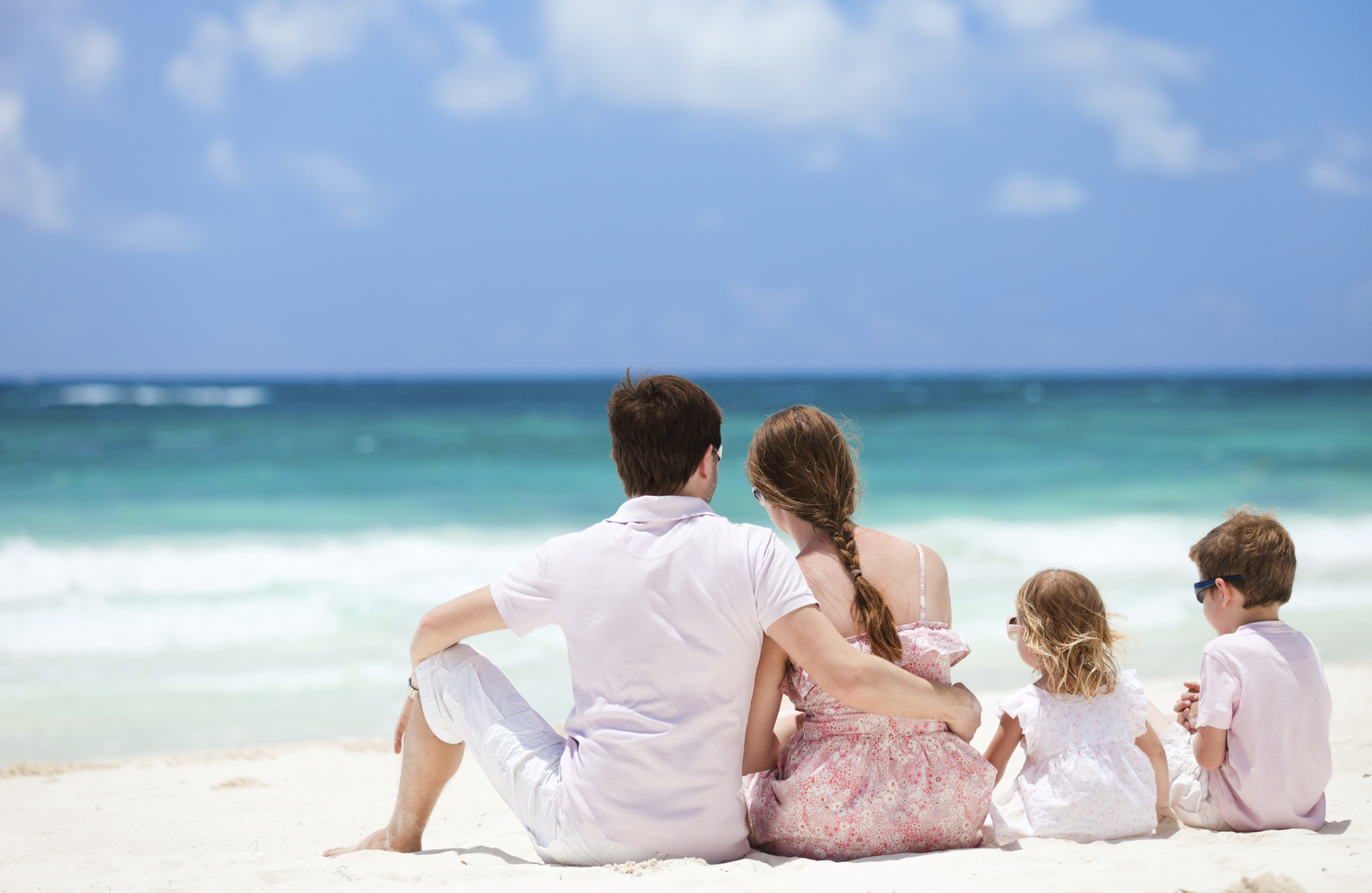 family sitting on a beach on vacation