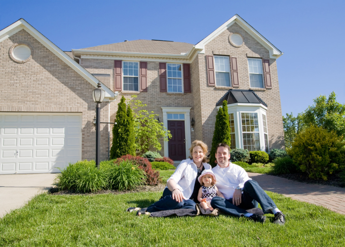 image of first time homebuyers in front of their house
