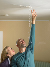 couple checking leaking ceiling